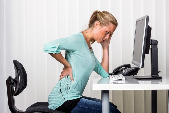 A woman sitting at a desk and has pain in the back.